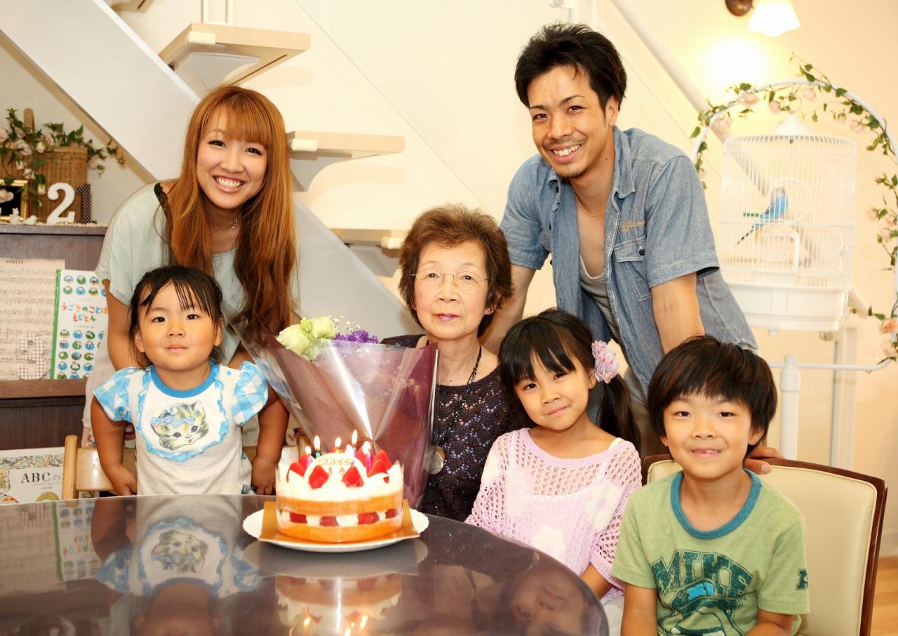 バースデーケーキを囲む祖母と親子