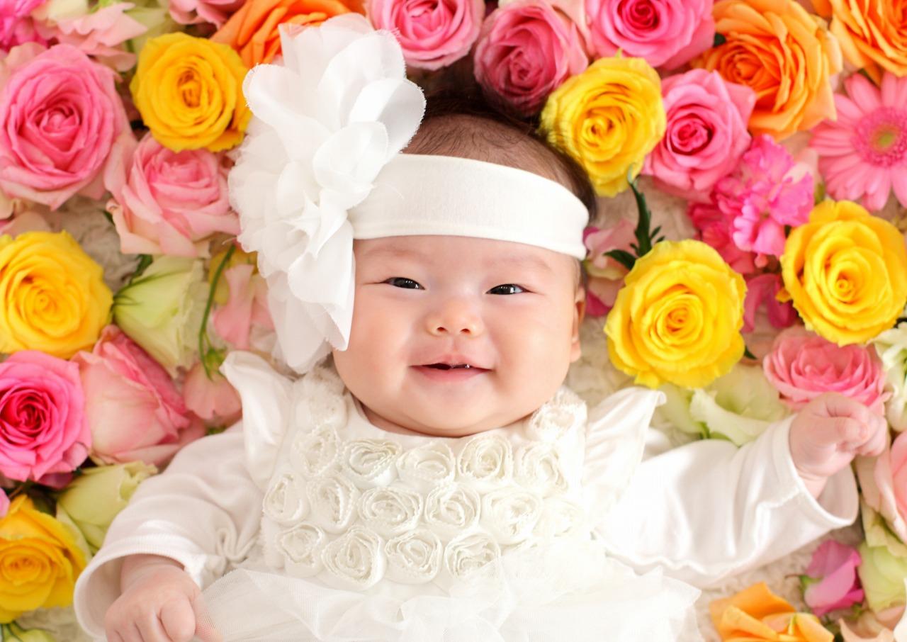 花に囲まれて笑う赤ちゃん