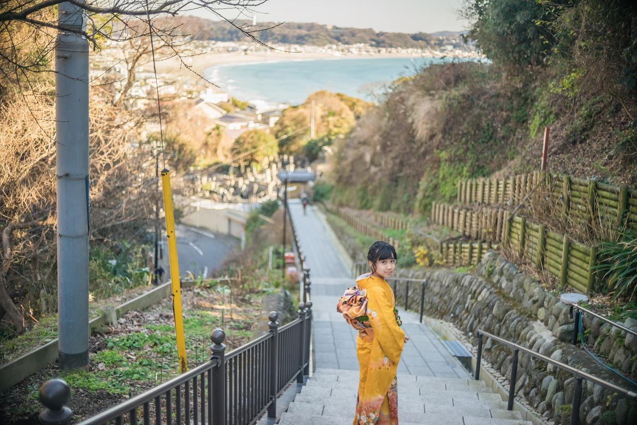 海を背景に立つ着物姿の少女